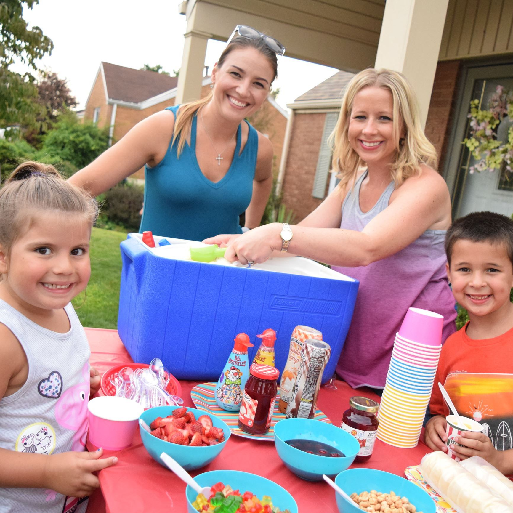 Mothers and children serve ice cream sundaes