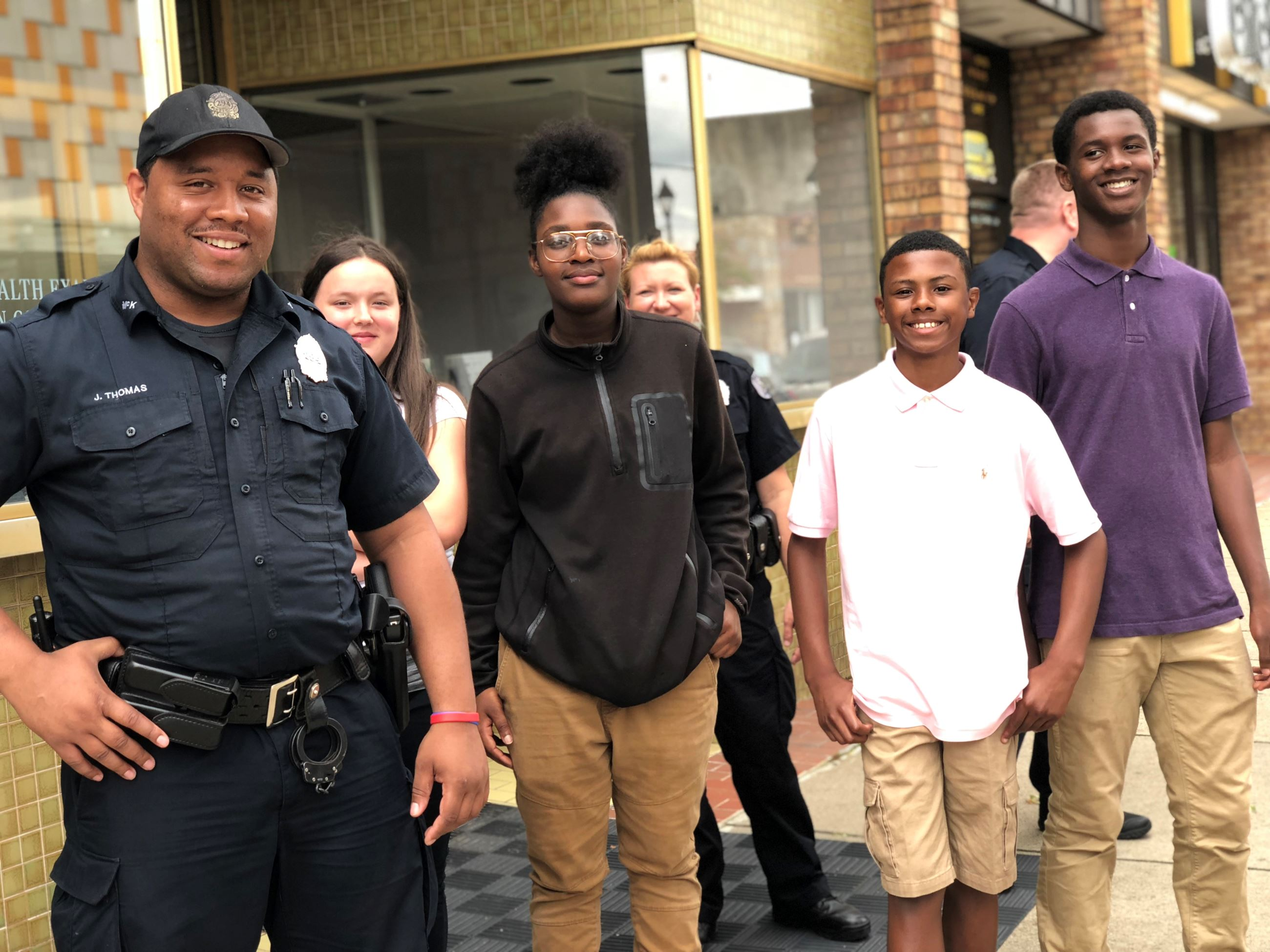 Students pose with police officer in business district