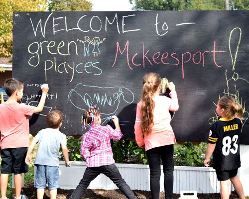 Children Drawing on Green Playces Chalkboard